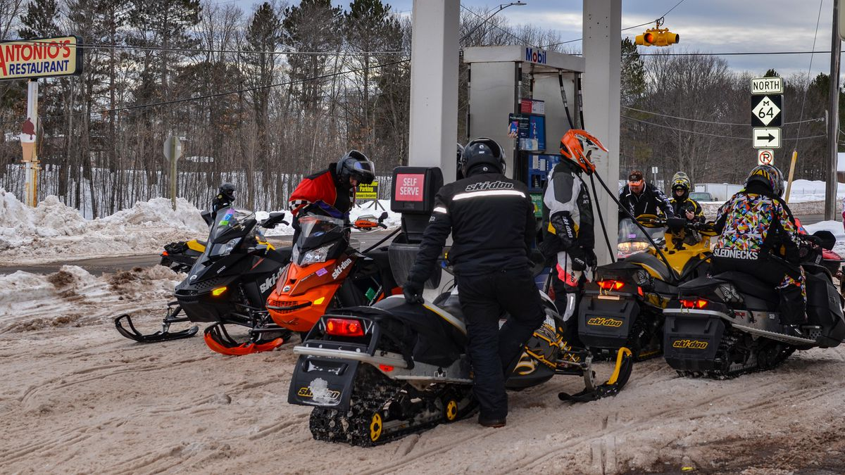 Snowmobilers gas up at a gas station in Bergland in Ontonagon County.