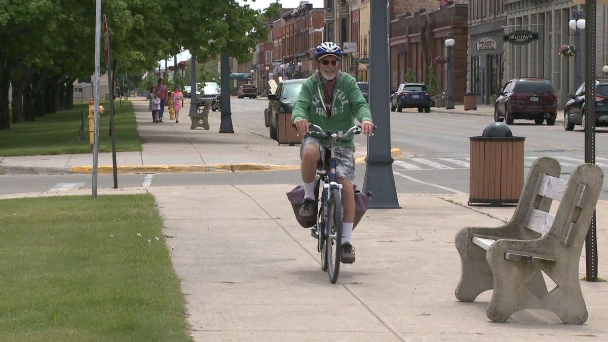 Man biking and people walking through downtown Menominee. (WLUC photo)