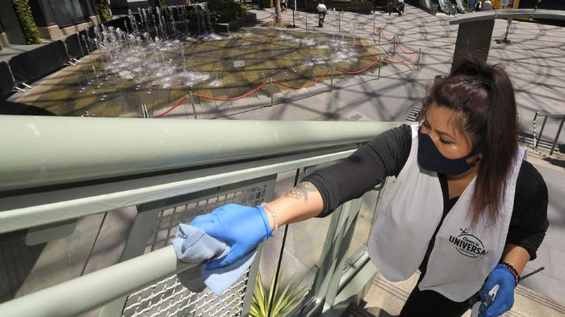 FILE - In this Thursday, June 11, 2020 file photo, Andrea Castaneda cleans the railings at...
