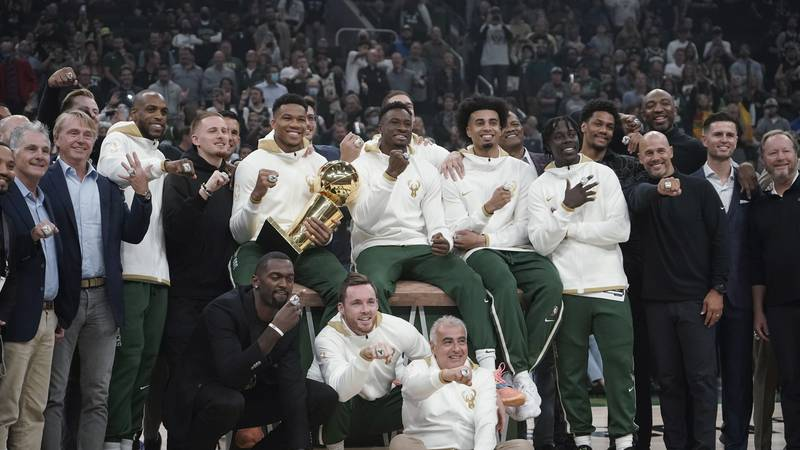 Milwaukee Bucks owners and players display their championship rings before an NBA basketball...