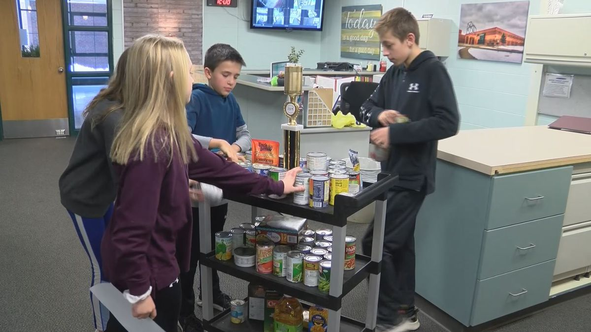 Kingsford Middle School Student Council Members arrange cans. (WLUC Photo)