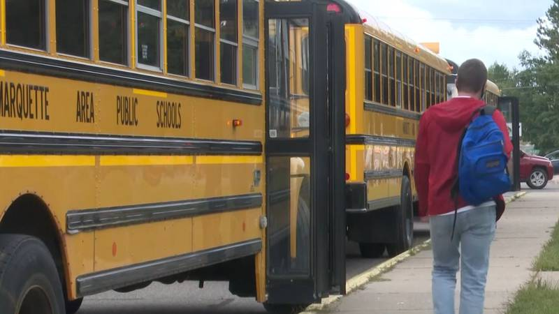 Marquette Area Public Schools' buses and a student.