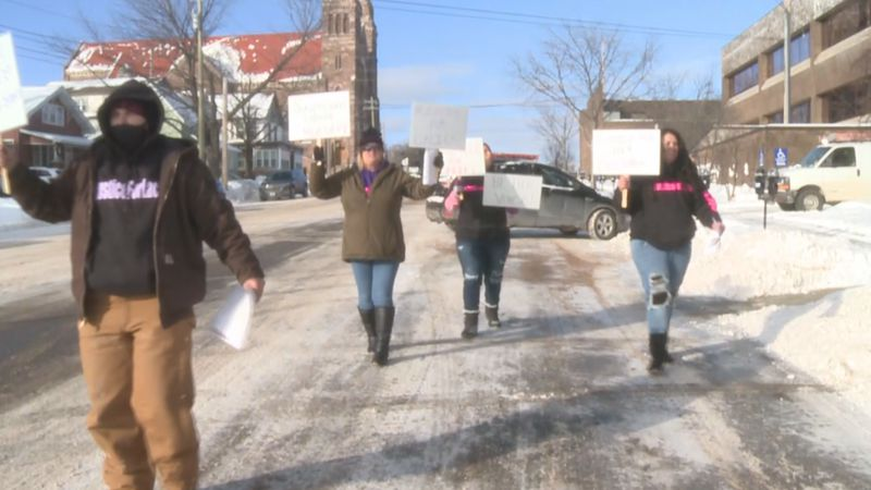 Lacie Borchert's friends and family march around the Marquette County Courthouse.