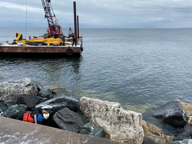 This photo shows the salvage barge along the breakwall in Marquette. The sunken tug is visible...