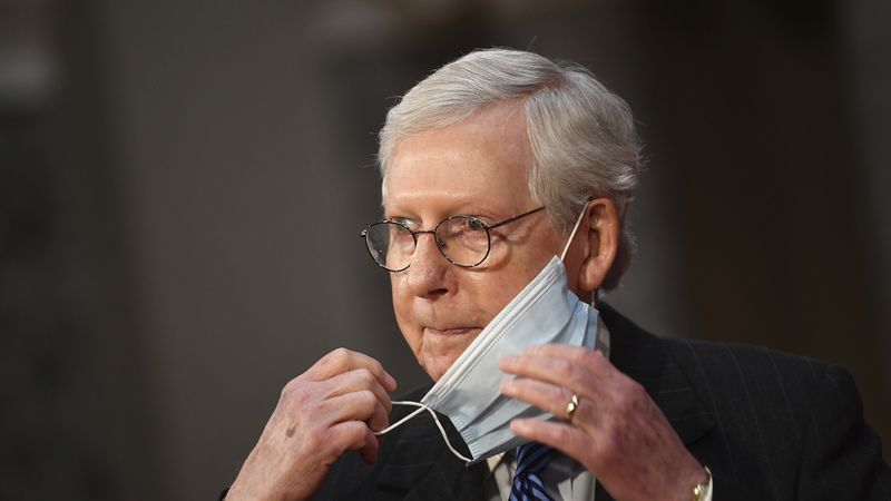 Sen. Mitch McConnell, R-Ky., adjusts his face mask as he participates in a swearing-in...