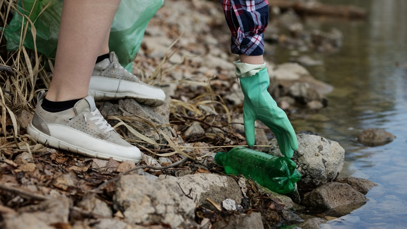 Cleaning up garbage along a river bank.