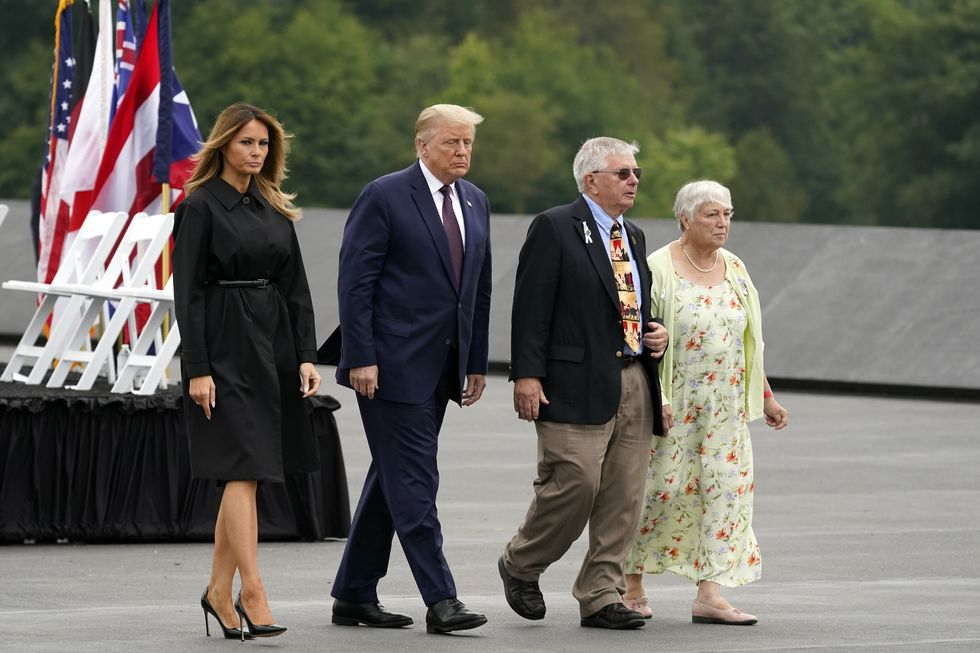 President Donald Trump and first lady Melania Trump walk with Ed Root and his wife Nancy to lay a wreath at a 19th anniversary observance of the Sept. 11 terror attacks, at the Flight 93 National Memorial in Shanksville, Pa., Friday, Sept. 11, 2020. Ed Root's cousin was flight attendant Lorraine Bay.