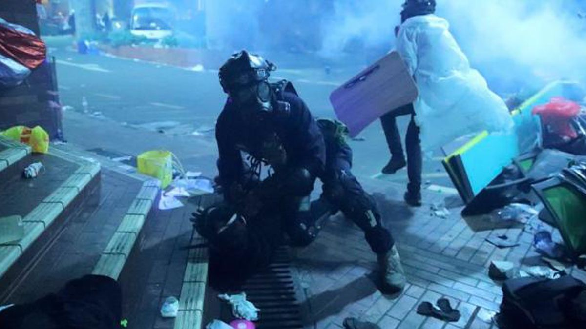 A policeman in riot gear detains a protester outside of Hong Kong Polytechnic University as police storm the campus in Hong Kong, early Monday, Nov. 18, 2019. Fiery explosions were seen early Monday as Hong Kong police stormed into a university held by protesters after an all-night standoff. (AP Photo/Kin Cheung) (Source: Kin Cheung)