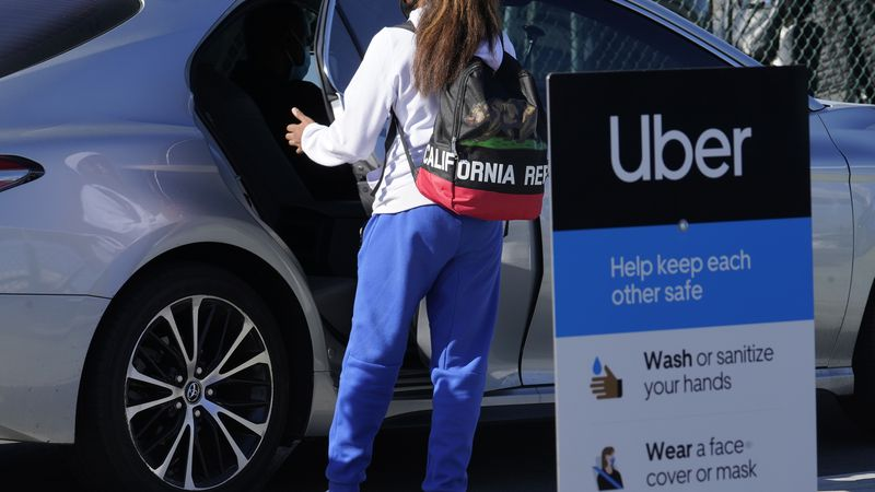 FILE - In this Nov. 13, 2020 file photo, a traveler rides in the back of an Uber vehicle at Los...