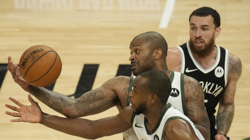 Milwaukee Bucks' P.J. Tucker and Khris Middleton steal the ball from Brooklyn Nets' Mike James...