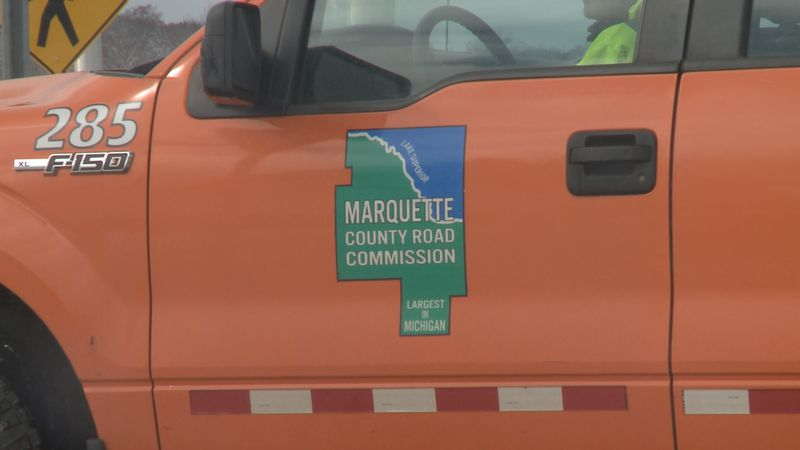 A Marquette County Road Commission truck driving through Ishpeming Township.