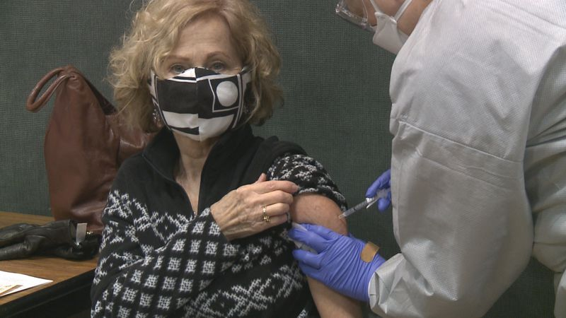 A woman receives the COVID-19 vaccine at Bay College.