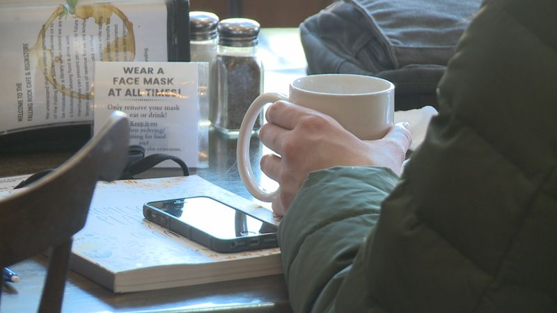 A customer enjoys a cup of coffee seated inside Falling Rock Café & Bookstore in Munising.