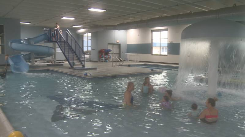 Children and parents swim in the pool.