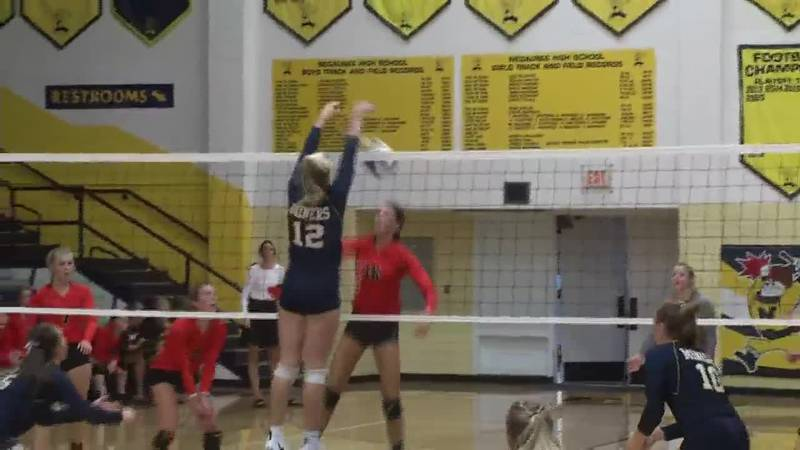 Negaunee's Natalie Bell rejects the attempt from Houghton's Stella Wickstrom in the second set