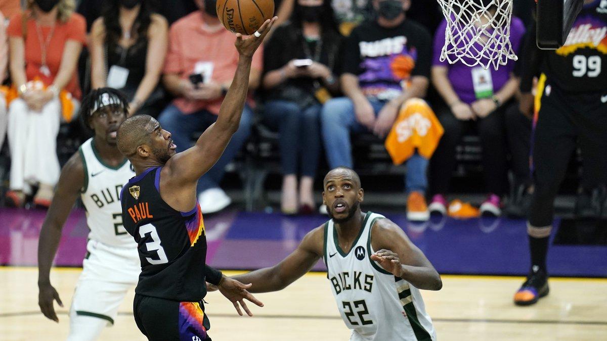 Phoenix Suns guard Chris Paul (3) scores as Milwaukee Bucks forward Khris Middleton (22) and...