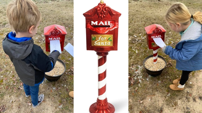 Two children drop off letters at Santa's Mailbox in Newberry, Michigan.