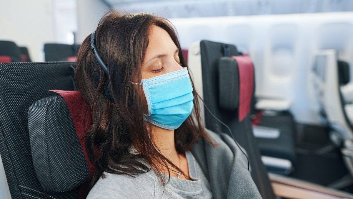 Woman wears face mask while resting before her flight takes off.
