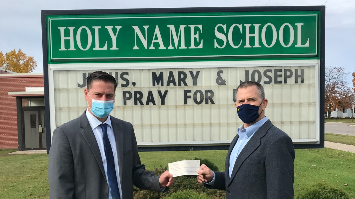 Principal of Holy Name Catholic School Joseph Carlson accepts a $178,964 donation from Todd C....