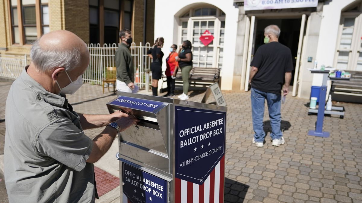 FILE - In this Monday, Oct. 19, 2020 file photo, a voter submits a ballot in an official drop...