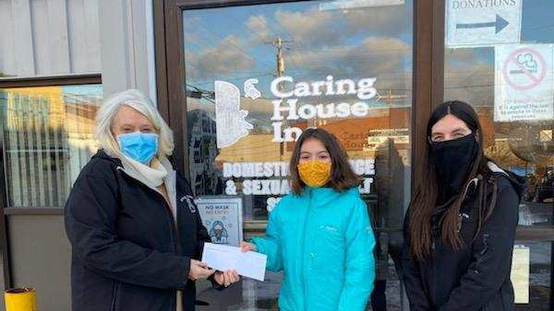 The Caring House's director Cheryl O'Neil, stands with Ella and the check. (Credit: Jesy DeRoche)