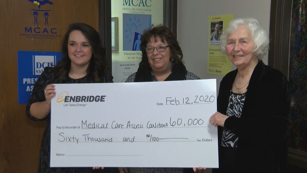 Emma Cook with Enbridge, Mylyn Trulock, the Director of MCAC, and Lola Johnson, the MCAC Board President stand with the check. (WLUC Photo)