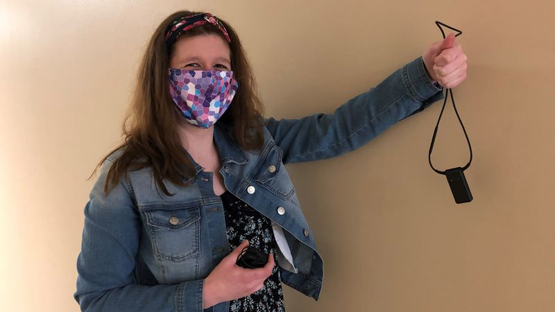 Olivia Anderson holding up her FM, a device that helps her hear her professors in classes.