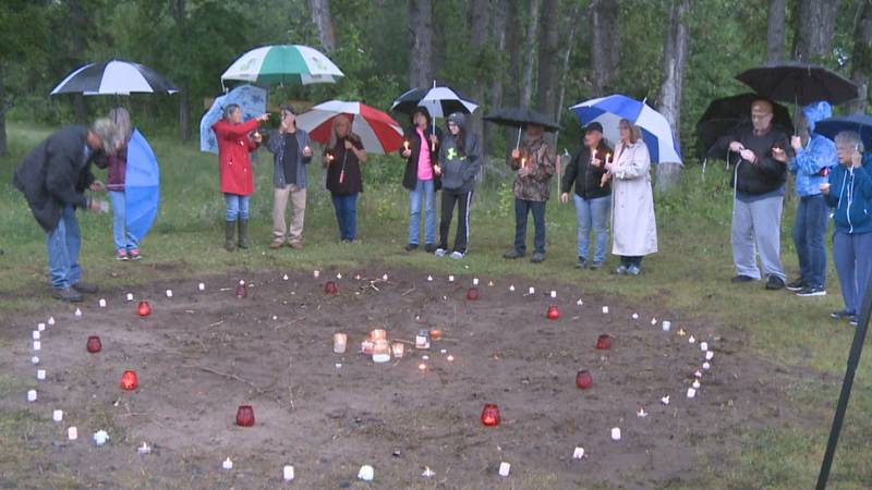 Residents hold candles around the former location of the gazebo.
