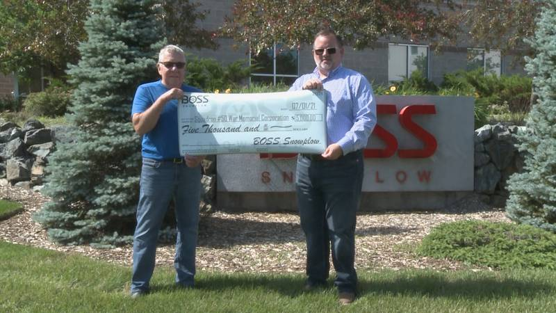 Boss Snowplow marketing director Mark Klossner hands the $5,000 check to a Sons of the American...