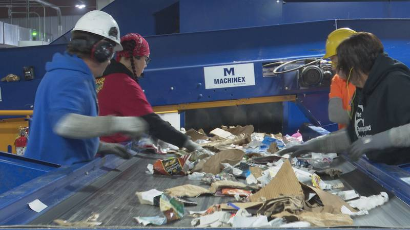 Employees at Recycle 906 sort items.