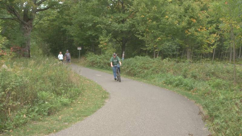 Community members walk and bike along the Iron Ore Heritage Trail in Negaunee.