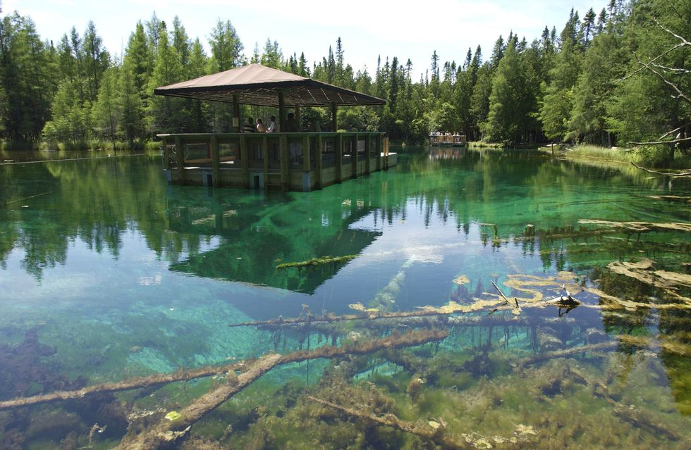 """The glass-bottomed raft over Kitch-iti-kipi, or the """"Big Spring,"""" at Palms Book State Park in..."""