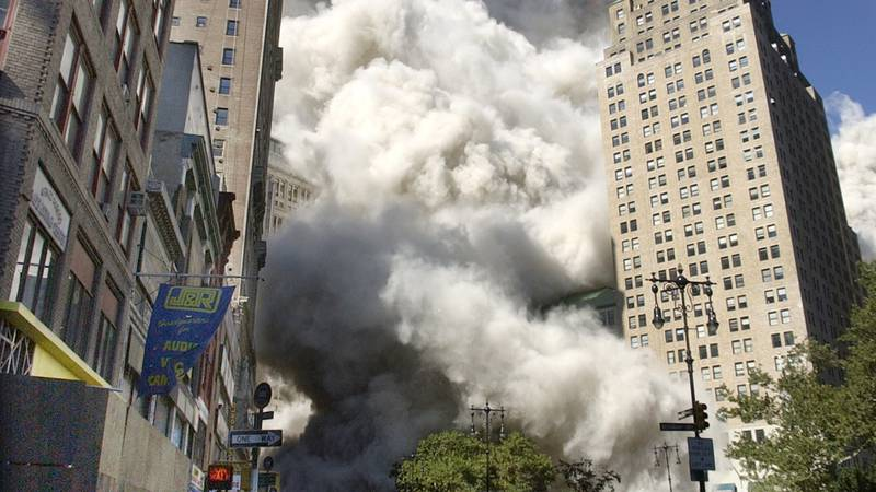 People flee the falling South Tower of the World Trade Center on Tuesday, September 11, 2001. ...
