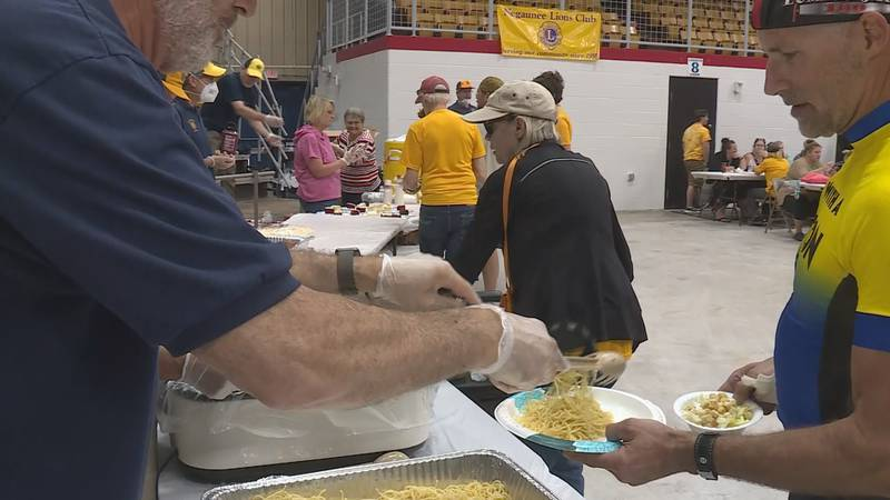 An Ore to Shore participant gets a plate of spaghetti from a Negaunee Lions Club member.