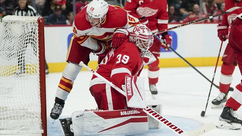 Calgary Flames left wing Matthew Tkachuk (19) hits Detroit Red Wings goaltender Alex...