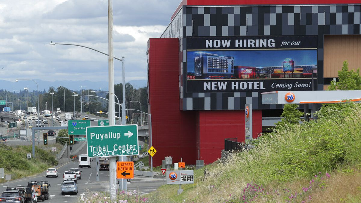 "In this July 9, 2020, file photo, a large video display reads ""Now hiring for our new hotel coming soon!,"" at the new Emerald Queen Casino, which is open, and owned by the Puyallup Tribe of Indians, in Tacoma, Wash. The number of laid-off workers applying for unemployment aid fell below 1 million for the first time since the pandemic intensified in March, though applications remain at an extraordinarily high level."