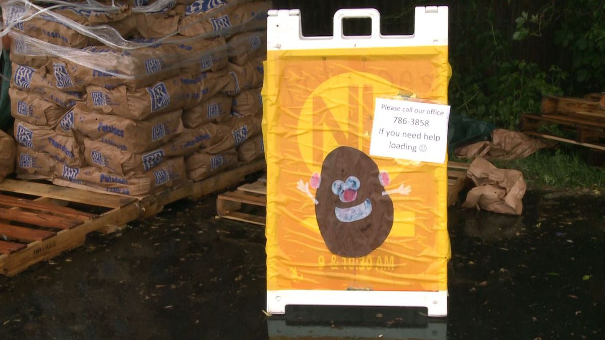 Sign made by New Life Church with pallets of potatoes in the back. (WLUC photo)
