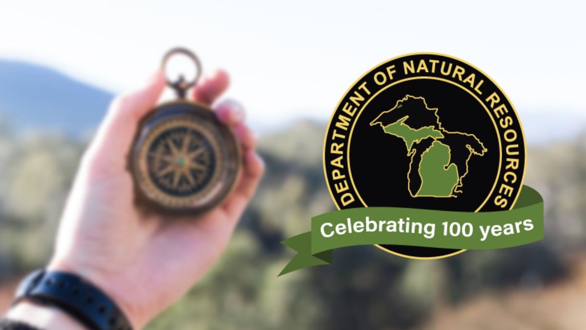 A blurred compass image with the Michigan Department of Natural Resources 100 years logo.