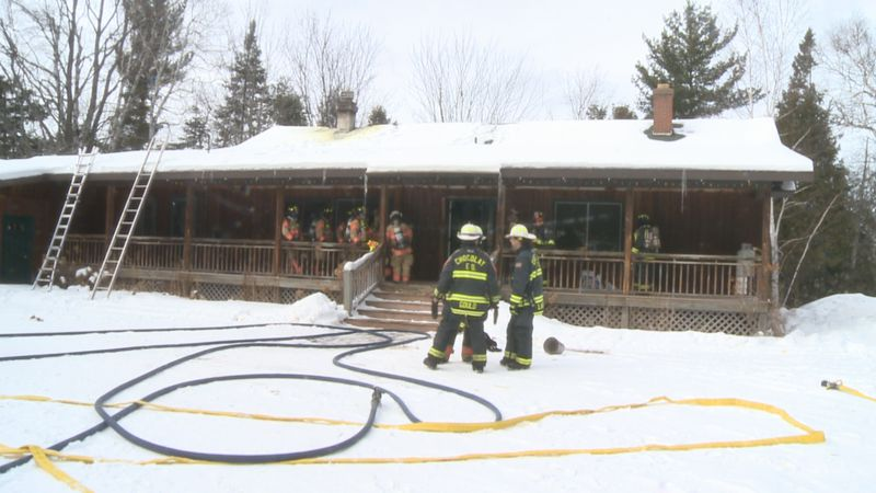 Three fire departments work to prevent further damage inside the house.