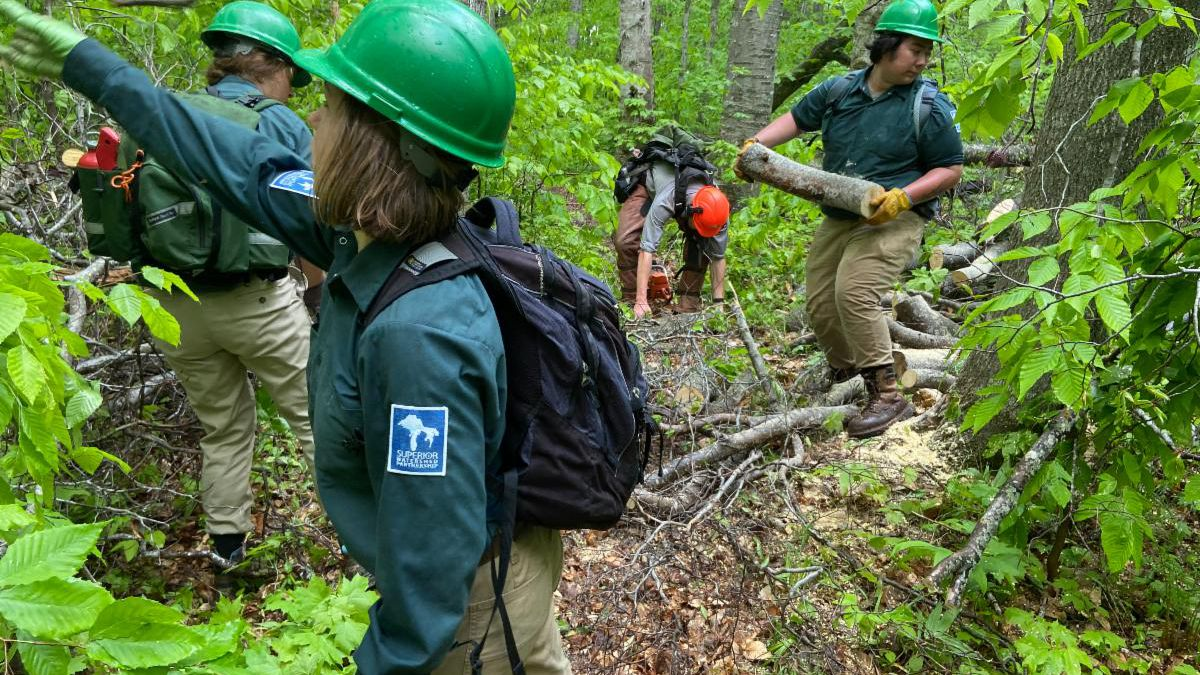 GLCC crew members Andrea Sekloch, Alayna Merchlewitz and Sena Parker (left to right) clear debris from trail at Pictured Rocks National Lakeshore. (Superior Watershed Partnership Photo)