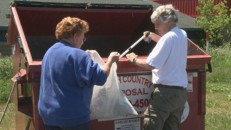 Rodgers and Hoover remove unwanted items from a community member's bag.