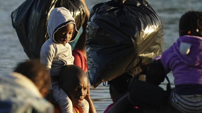 Migrants cross the Rio Grande river to Del Rio, Texas, from Ciudad Acuna, Mexico, early...