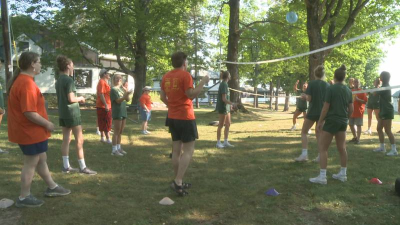 Campers play volleyball with the Northern Michigan University women's team.