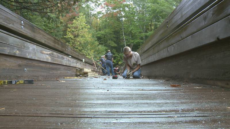 Volunteers remove old pieces of the walkway before installing new ones.