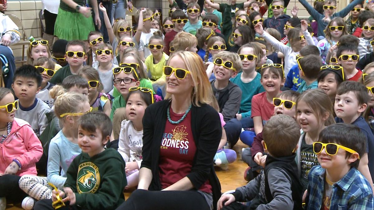 Spread Goodness Day sunglasses seen on kids in an elementary school, and Anna Dravland, on Spread Goodness Day 2019. (WLUC Photo)