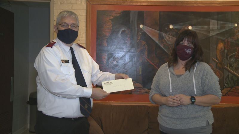 Marquette County Salvation Army Captain Doug Winters accepts a check from Kori Tossava of the...