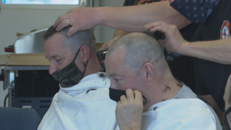 The two departments came together to shave their heads to support children with cancer.