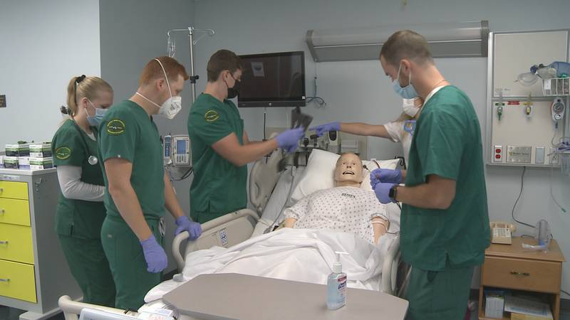 Nursing students Brandalyn, Ben, Jeremy, and Mike practice their skills in a nursing lab.